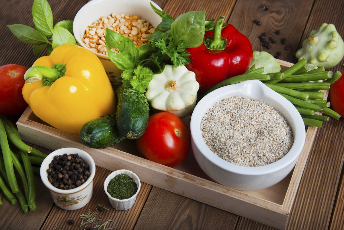 Health food with high fibre. Dietting, whole wheat cerals, grains, vegetables, antioxidants and vitamins: zzuchini, tomatoes, cucumbers, beans. Rustic wooden background top view.